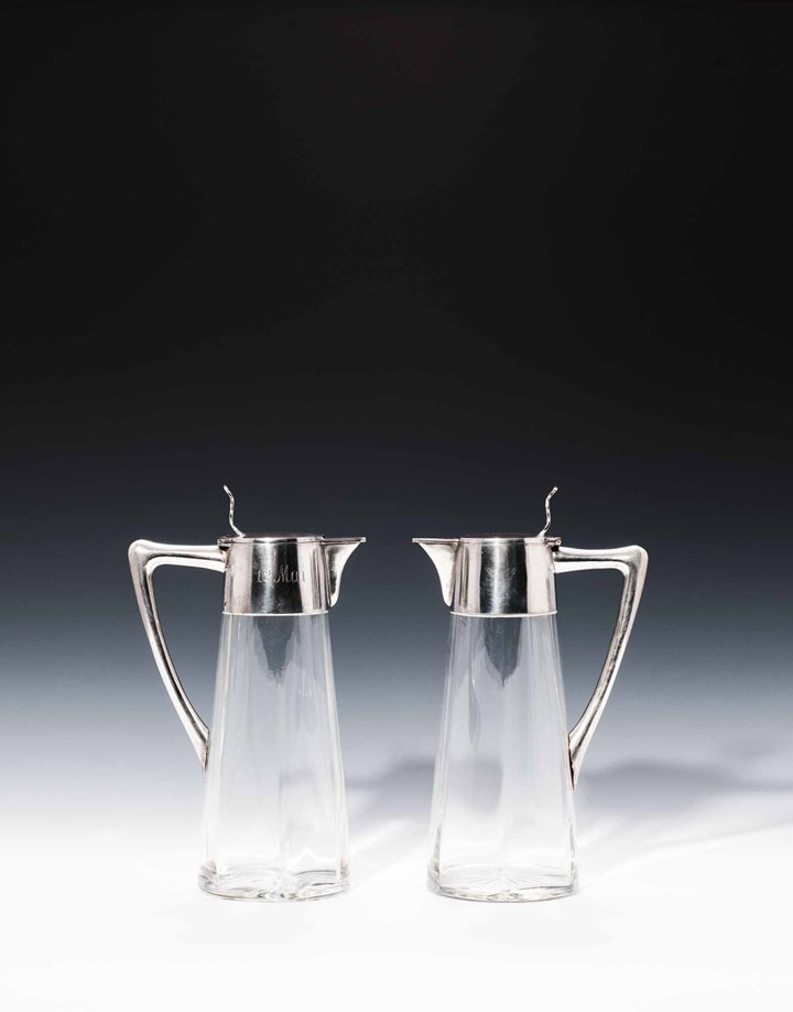 A PAIR OF JUGS WITH SILVER MOUNTS