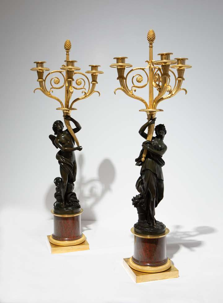 A Pair of three-branch ormolu Candelabra with patinated bronze figures of Zephyrus and Flora, on rouge griotte marble columns