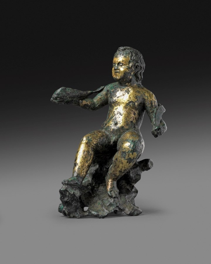Statuette depicting a rare iconography of the god Eros, sitting on a rock and holding a fish