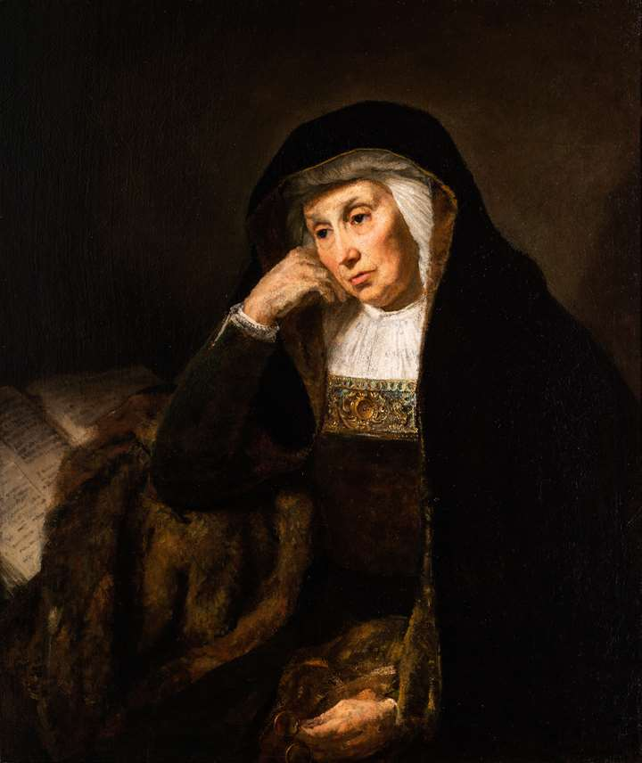 An Old Woman reading at a table.