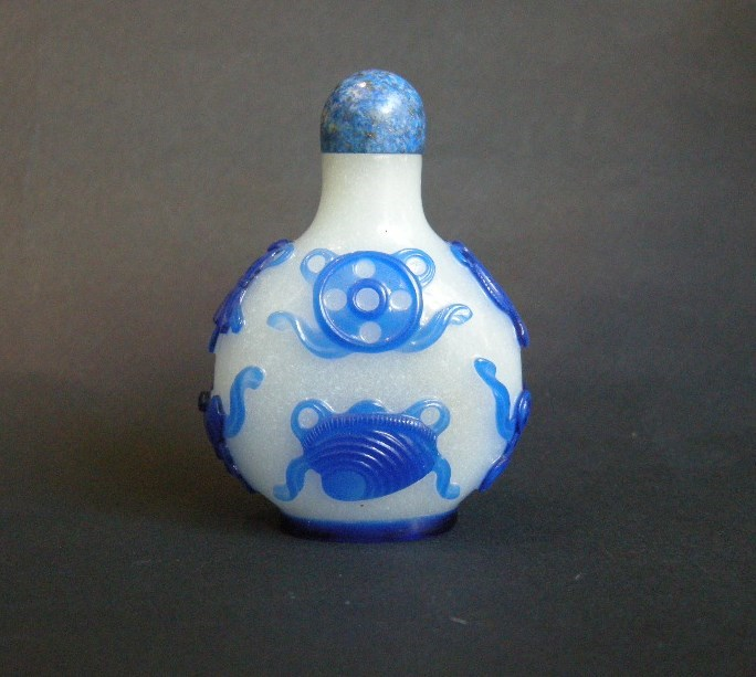 Snuff bottle glass overlay blue sculpted with eight bouddhist emblems on white ground