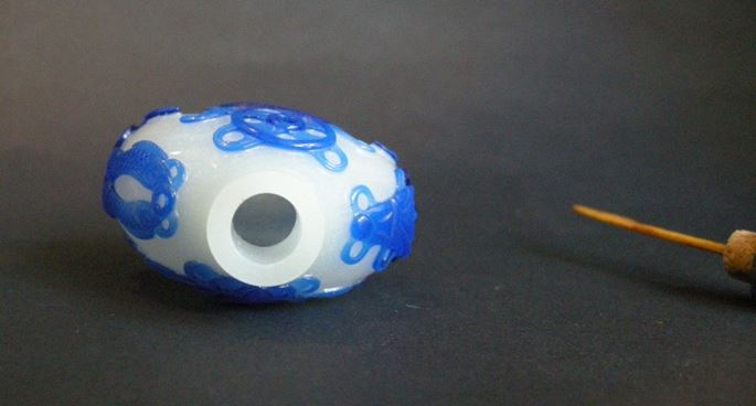 Snuff bottle glass overlay blue sculpted with eight bouddhist emblems on white ground | MasterArt