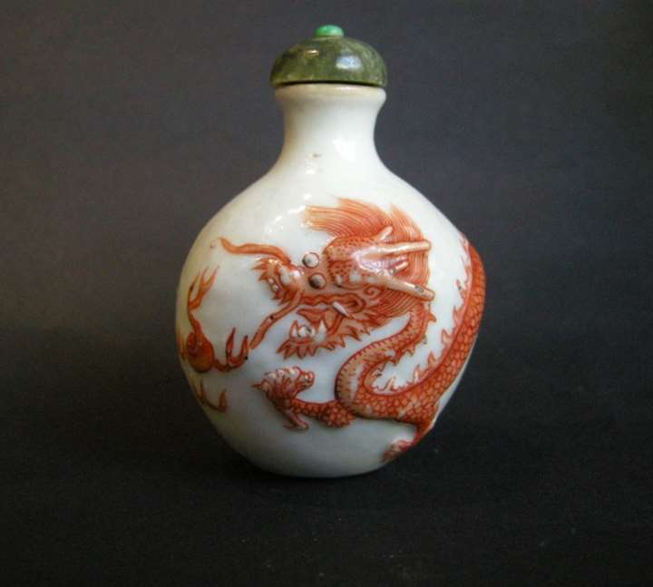 Snuff bottle porcelain with a low relief a Dragon in iron red