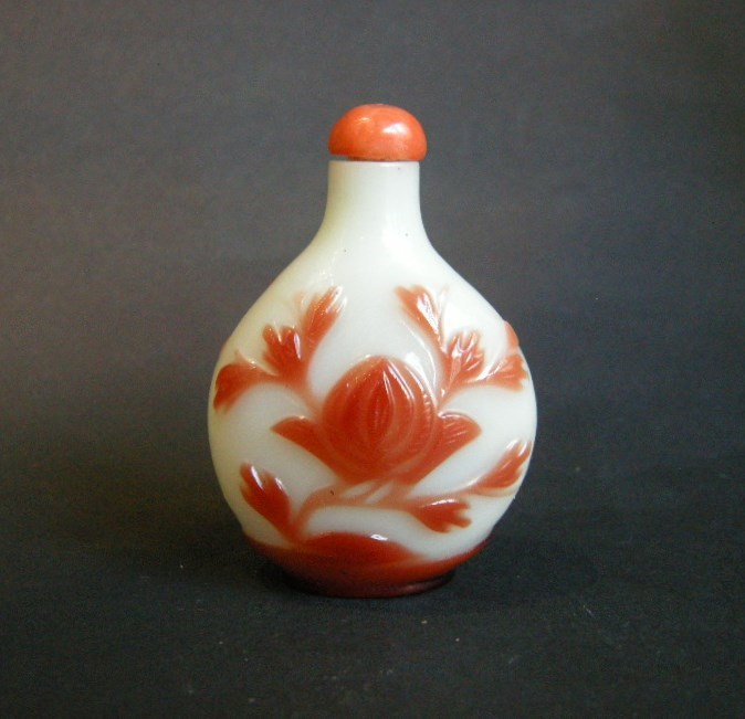 Snuff bottle glass red overlay on ground white sculpted with flowers. Probably Yangzhou school