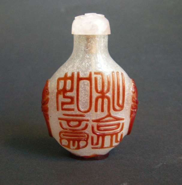 Snuff bottle glass  overlay red with caligraphy on a face  and box and lotus  other face