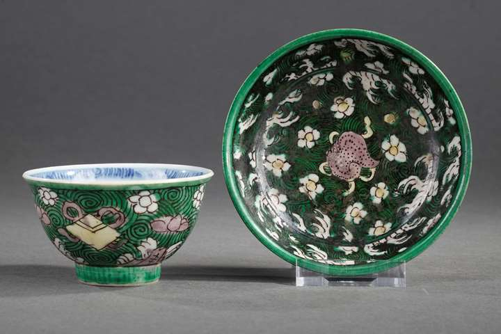 Cup and saucer Famille Verte porcelain with precious things and flowers on waves ground