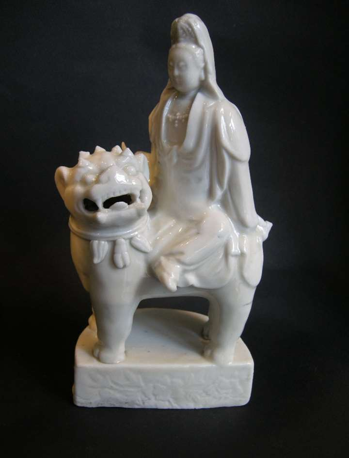 Figure showing a guanyin seated on a buddhist lion in blanc de chine porcelain
