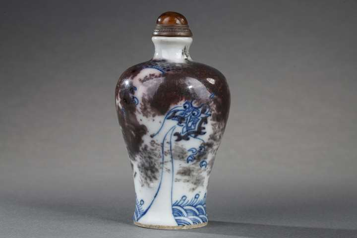 Snuff bottle porcelain enamelled in underglaze blue and copper red decorated with a Dragon in a clouds