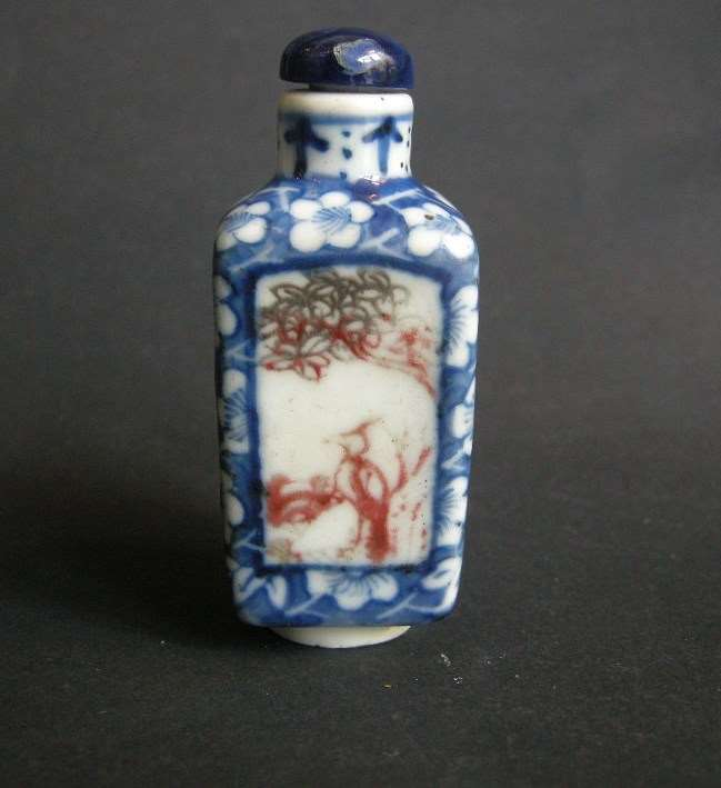 Snuff bottle porcelain quadrangular shape  decorated in underglaze blue with prunus flowers and for panels in copper red  with birds and insects in a landscape