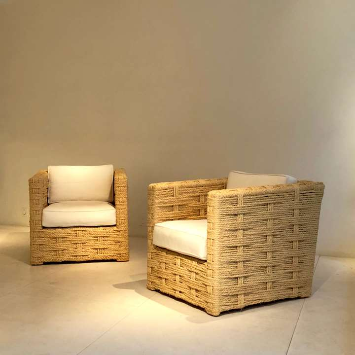 Pair of chairs and two ottomans, wooden structure trimmed with braided raffia