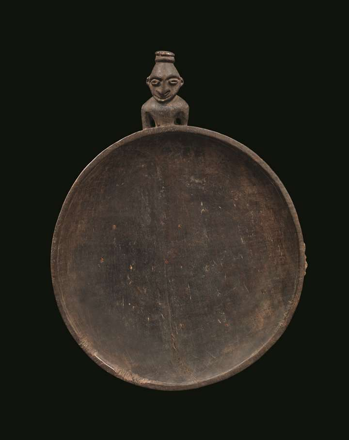 A very fine and early food dish carved with a stylized ancestor figure projecting from one edge