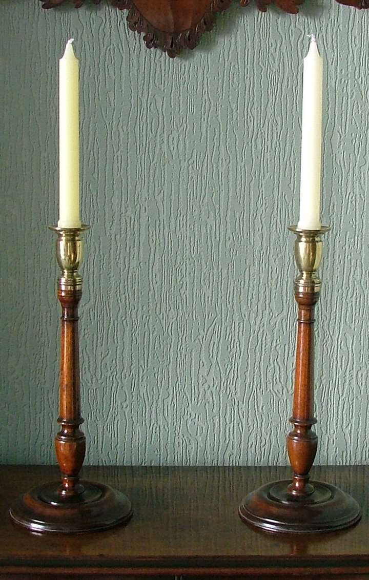 A FINE PAIR OF GEORGE II WALNUT AND BRASS CANDLESTICKS