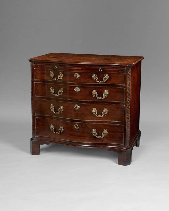 A George III period mahogany serpentine commode