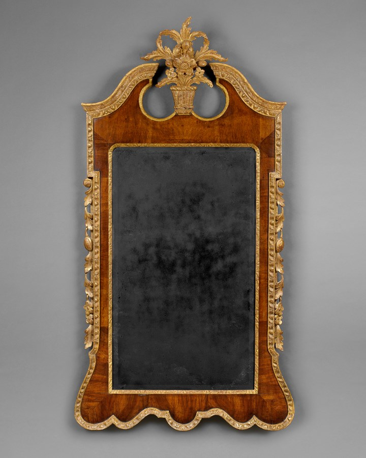 A LARGE GEORGE II PERIOD VENEERED WALNUT AND CARVED GILTWOOD UPRIGHT WALL MIRROR