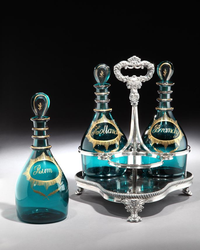 A SET OF THREE GEORGE III GREEN GLASS DECANTERS IN A SILVER PLATED STAND | MasterArt