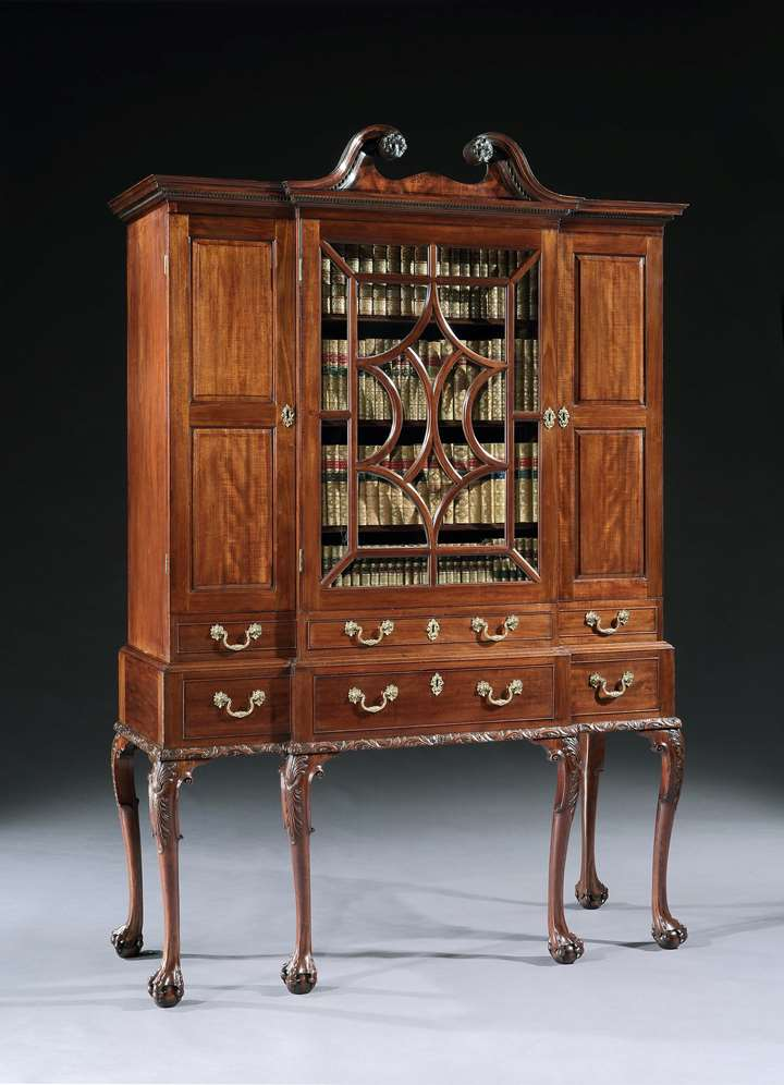 A GEORGE II MAHOGANY BREAKFRONT SECRÉTAIRE CABINET ON STAND