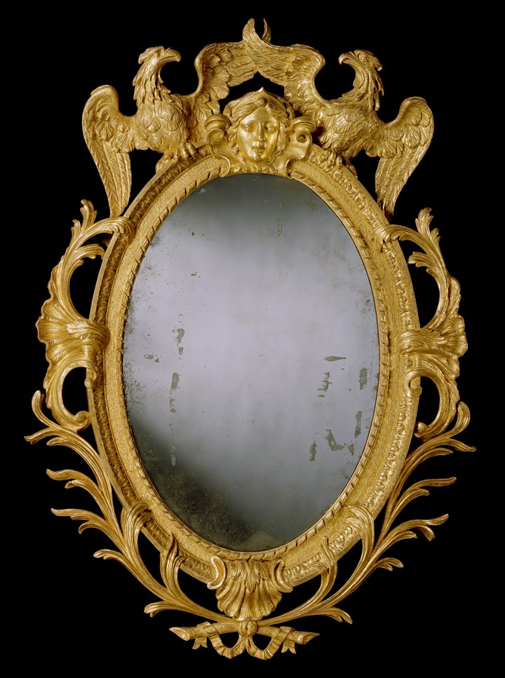 A GEORGE II CARVED GILTWOOD OVAL MIRROR