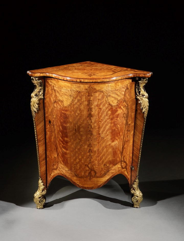A GEORGE III ORMOLU MOUNTED SATINWOOD CORNER CUPBOARD
