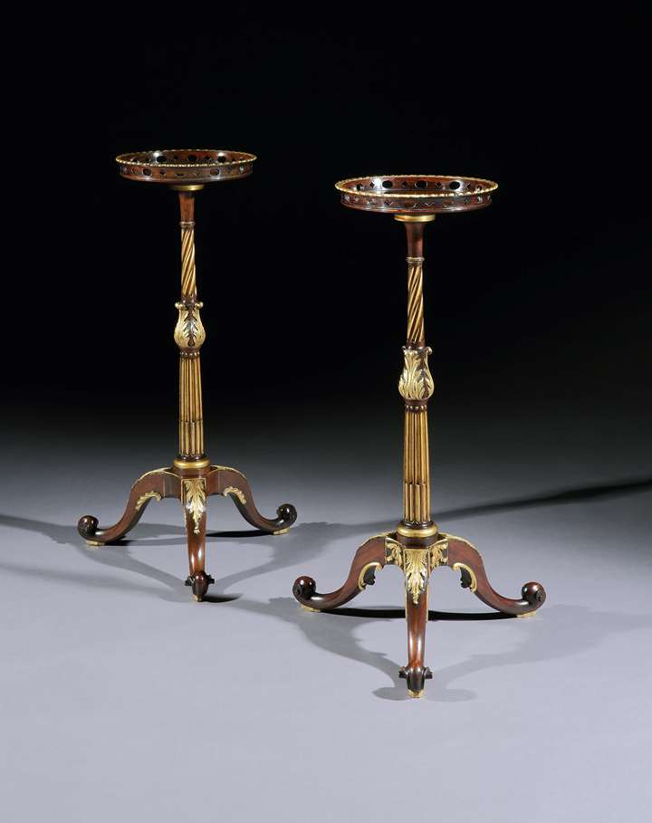 A near pair of parcel gilt mahogany torchères