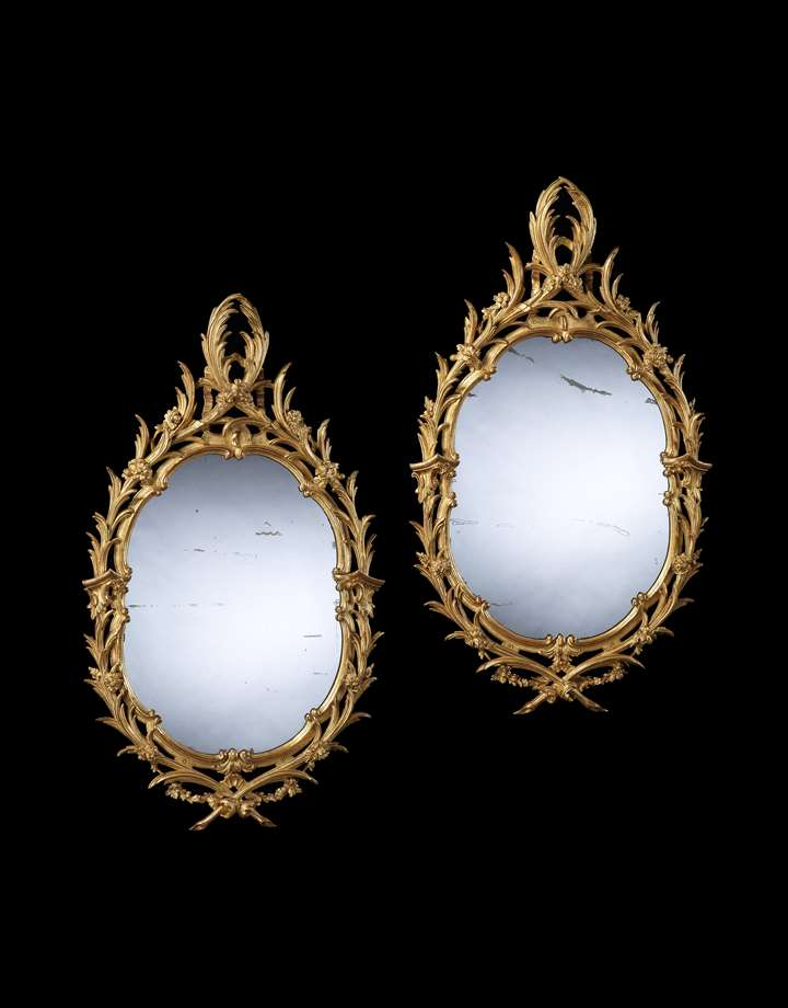 A PAIR OF GEORGE II OVAL GILTWOOD MIRRORS
