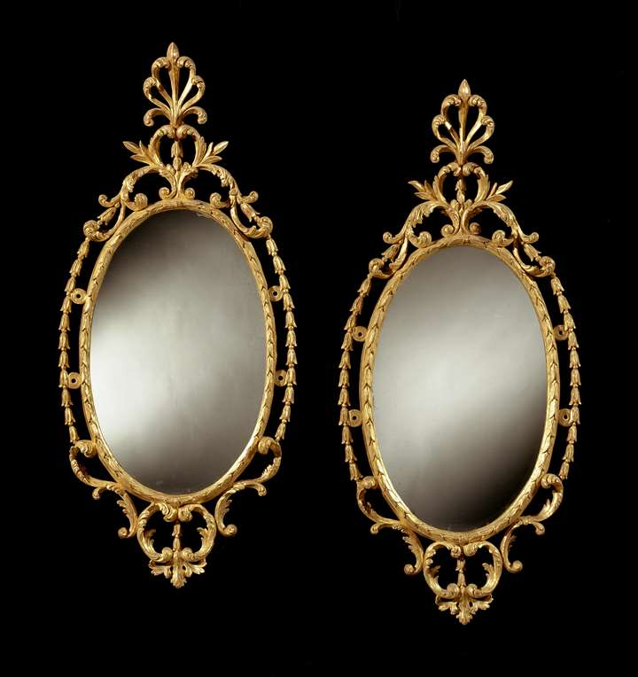 A PAIR OF GEORGE III OVAL GILTWOOD MIRRORS