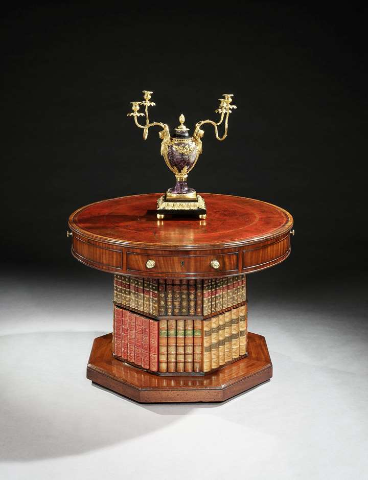 A regency mahogany revolving drum table on a bookcase pedestal