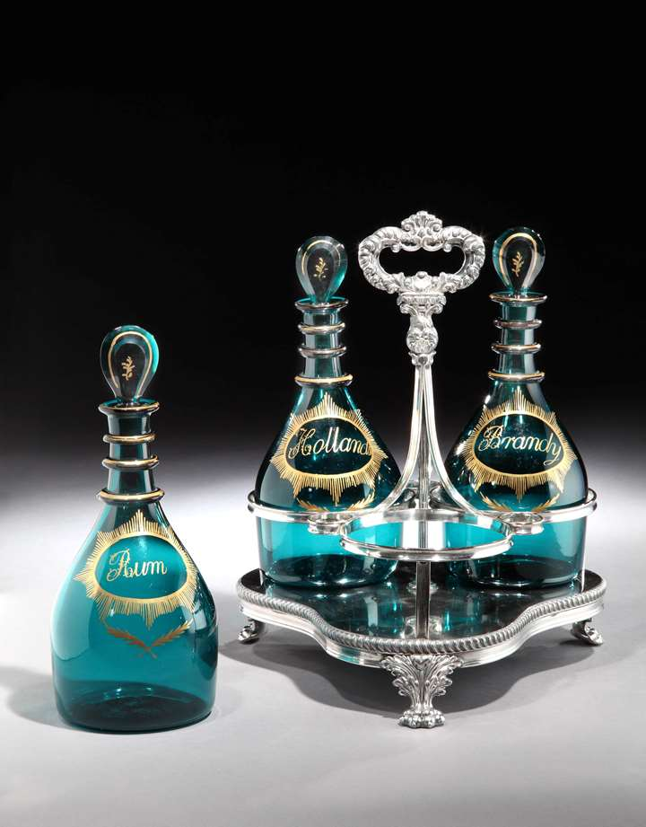 A SET OF THREE GEORGE III GREEN GLASS DECANTERS IN A SILVER PLATED STAND