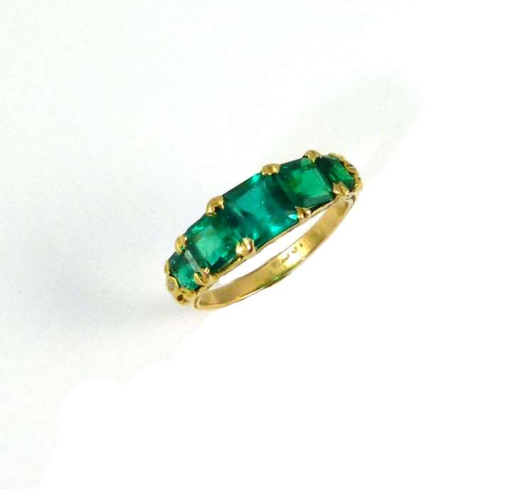 An antique emerald five stone ring.