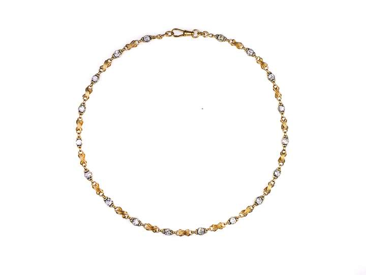 Antique gold and diamond chain necklace, 18 cushion cut diamond collets with stylised figure-of-eight gold scroll sections between