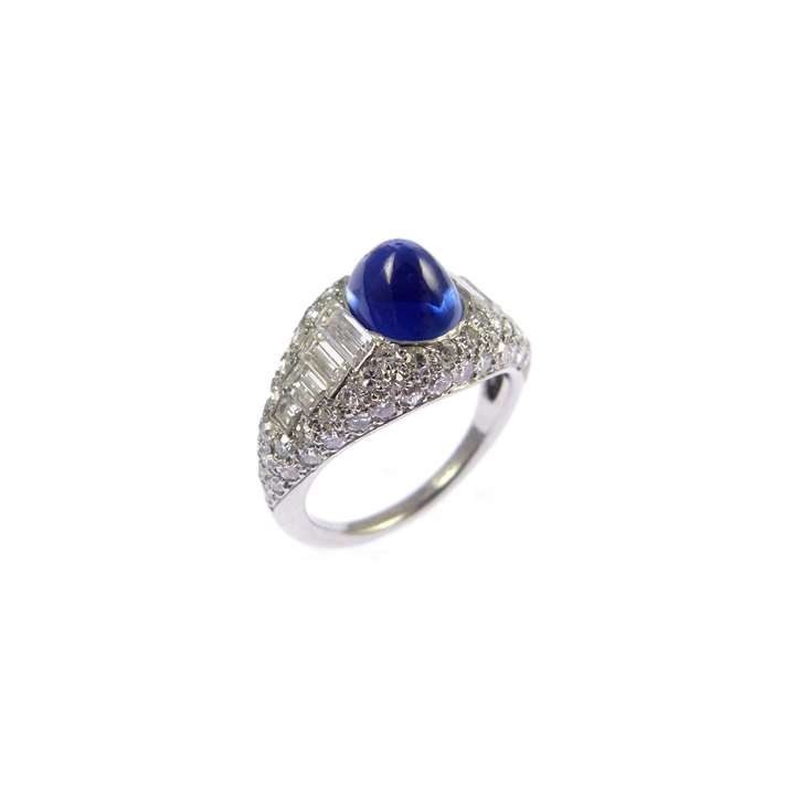 Cabochon sapphire and diamond cluster ring centred by an oval Kashmir sapphire