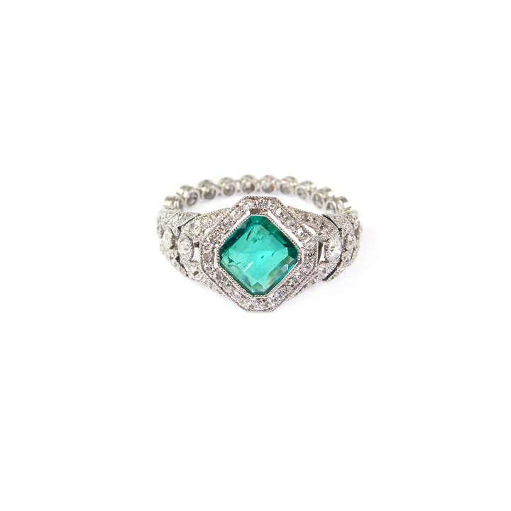 Early 20th century emerald and diamond cluster ring with flexible shank