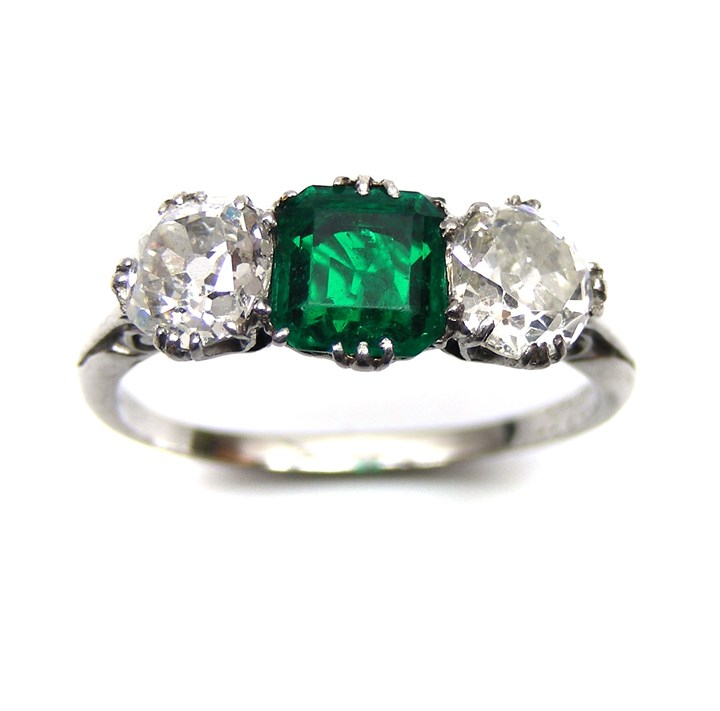 Emerald and diamond three stone ring with a central square cut emerald and a diamond on each shoulder mounted in a platinum mount with scroll shoulders