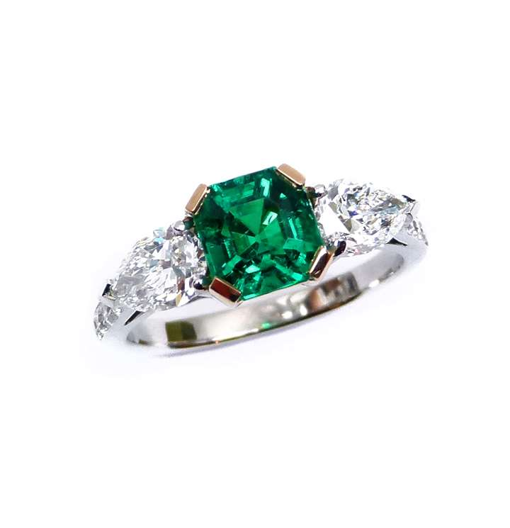 Emerald and diamond three stone ring, centred by a square trap cut emerald