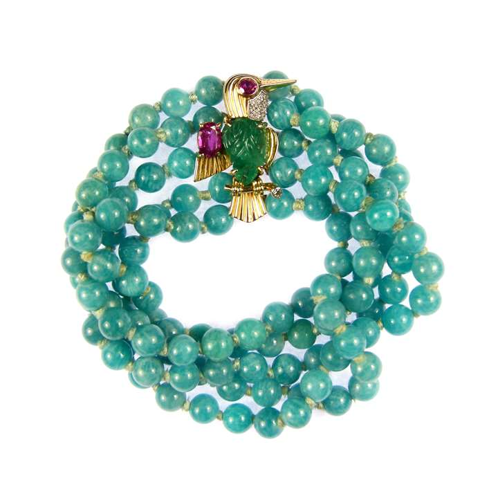 Emerald, ruby and diamond bird brooch clasp on a multi-row amazonite bead bracelet