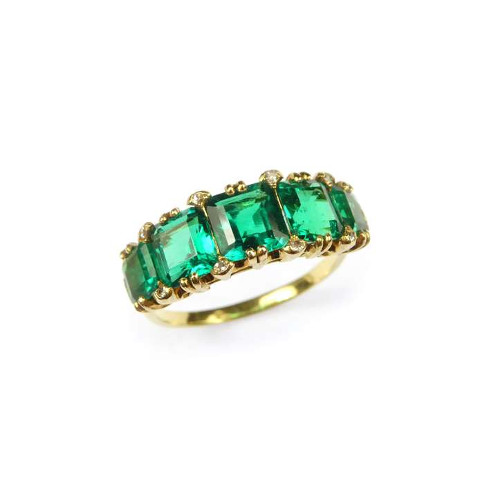 Graduated five stone emerald ring. claw set with trap-cut square Colombian emeralds