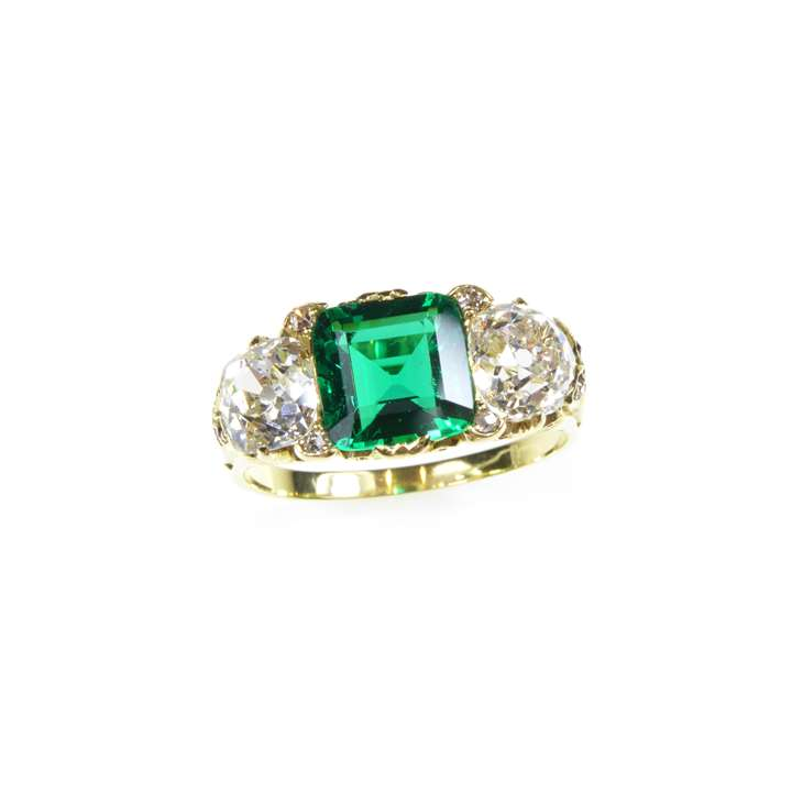 Emerald and diamond three stone ring  centred by a square cut Colombian emerald