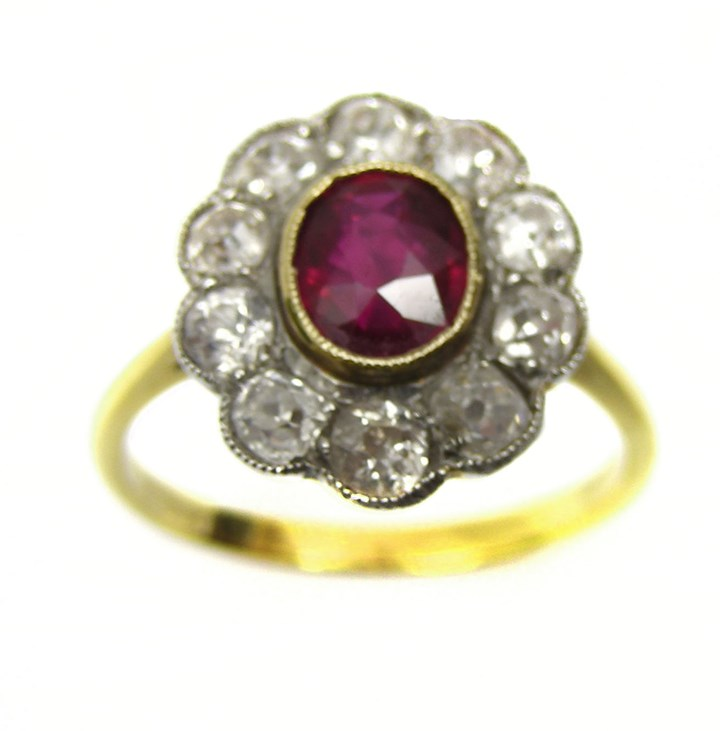 Oval ruby centre and diamond line border cluster ring