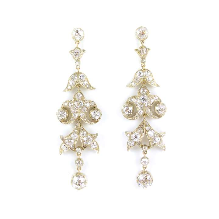 Diamond scroll cluster pendant earrings each hung with a cushion cut diamond collet