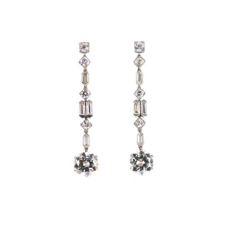 Pair of diamond pendant earrings of geometric design, each hung with a principal round brilliant cut diamond
