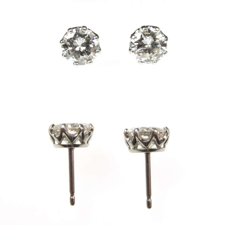 Pair of diamond stud earrings, 1.24cts and 1.22cts, claw set in coronet mounts