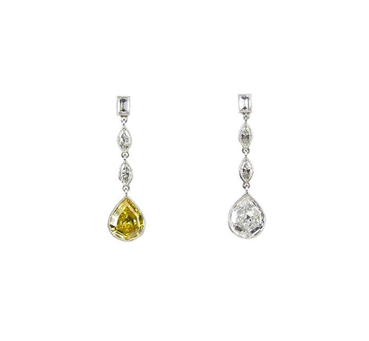 Pair of fancy pear shaped canary yellow and white diamond pendant earrings