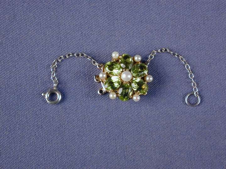 Peridot and pearl circular cluster snap with a central pearl and six oval peridots