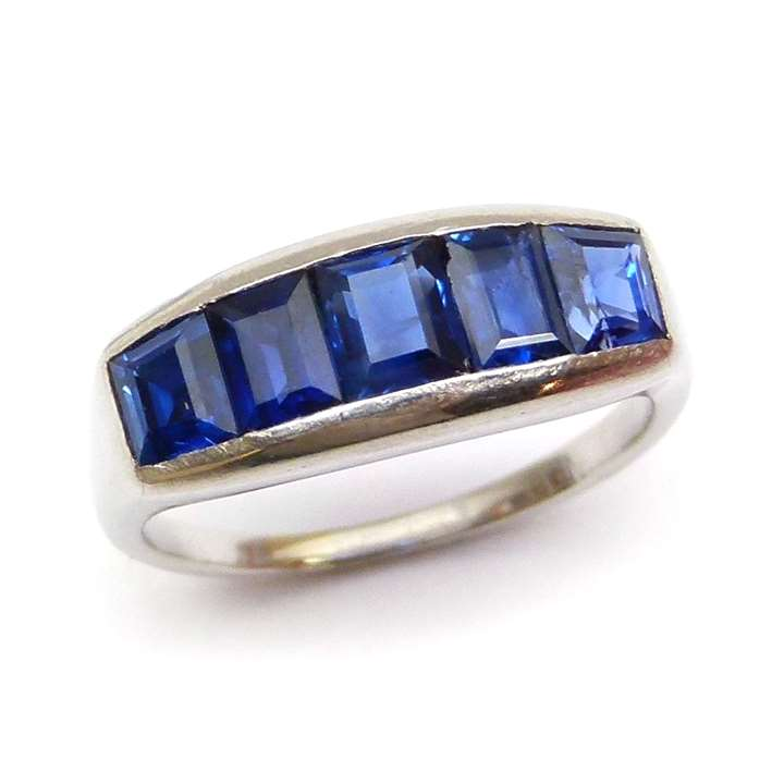 Platinum mounted plain half hoop ring with five rectangular cut sapphires