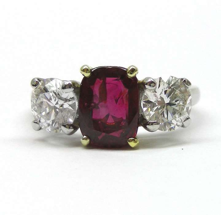 Platinum, ruby and diamond three stone ring, the central cushion-cut ruby of 1.64cts