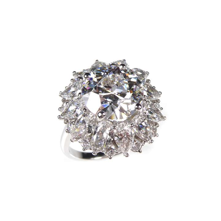 Round brilliant cut diamond and pear diamond cluster ring
