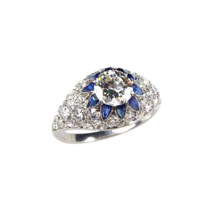 Round brilliant cut diamond bombe cluster ring, with sapphire accents