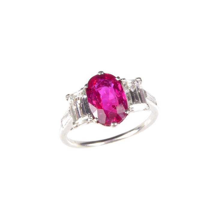 Ruby and diamond three stone ring,  claw set with an oblong Burma ruby.