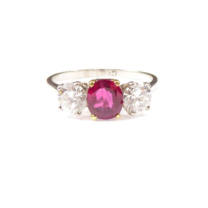 Ruby and diamond three stone ring, claw set with an oval cut Burma ruby,