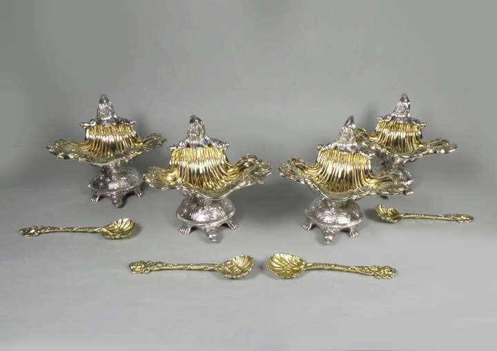 Set of four George III parcel git silver shell salts by John Craddock & William Reid, London 1818, together with four similar gilt shell spoons, London 1819,