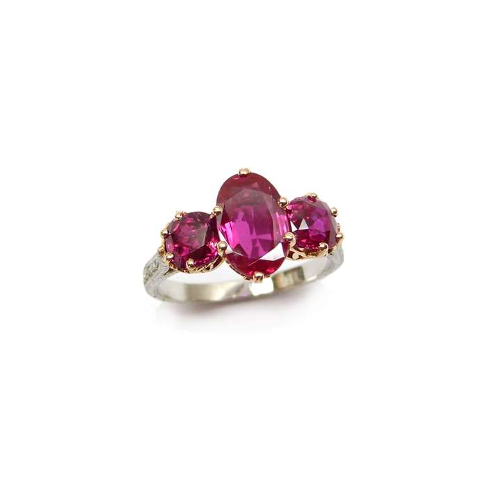Three stone Burma ruby ring, centred by an oval ruby of 2.16ct